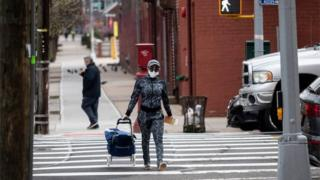 A woman wearing a mask crosses a road in Queens, New York (30/03/20)