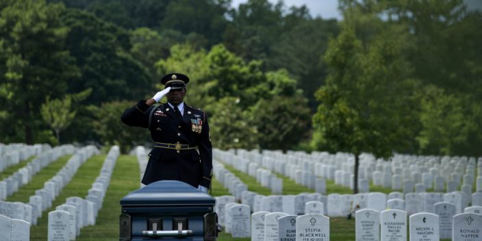 A US Army noncommissioned officer salutes as a World War II veteran is laid to rest at Arlington National Cemetery.