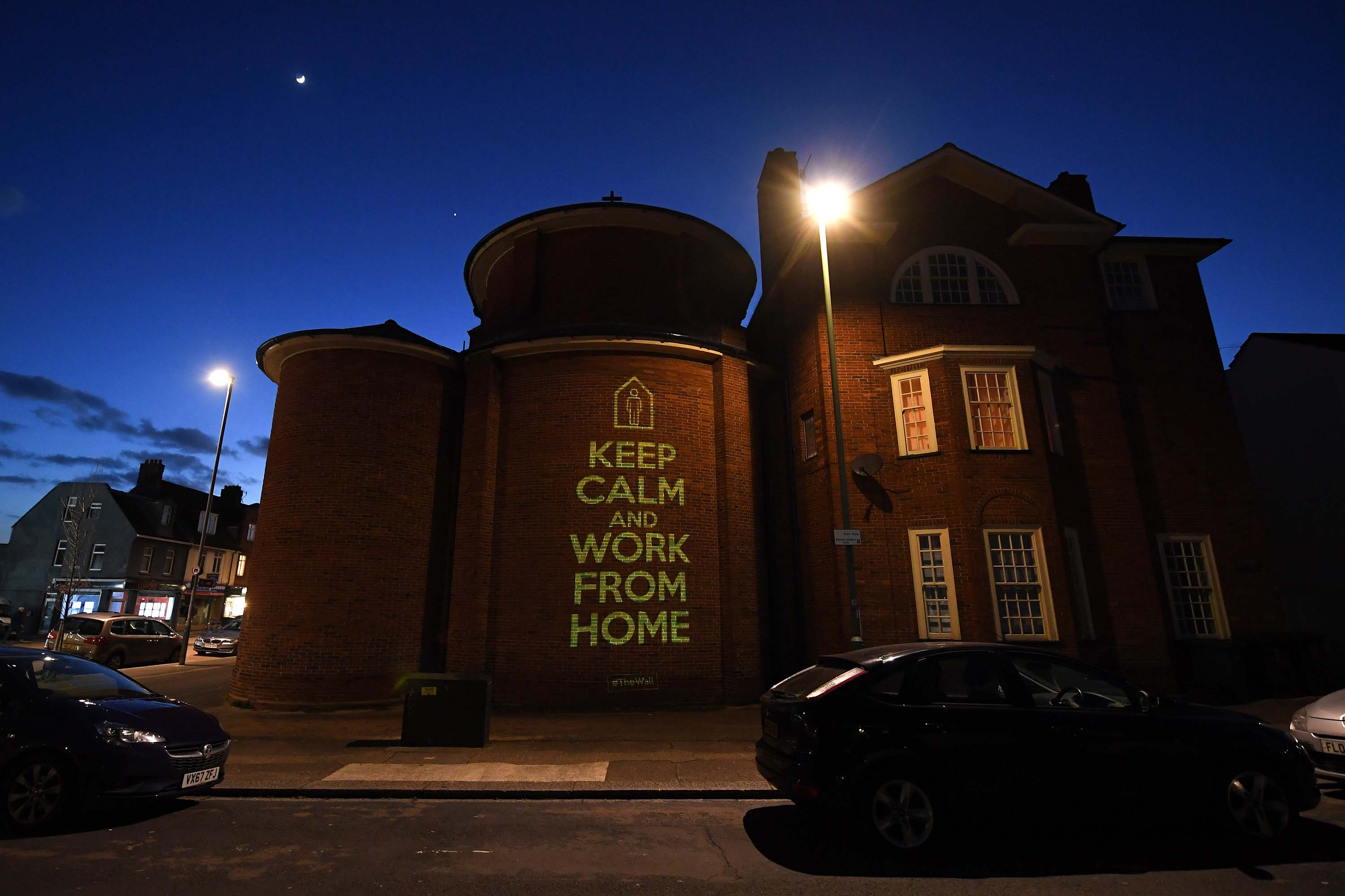 A message of 'Keep Calm And Work From Home' by artist Mike Dicks is projected onto a wall of a church in Brighton & Hove, England, on March 29.