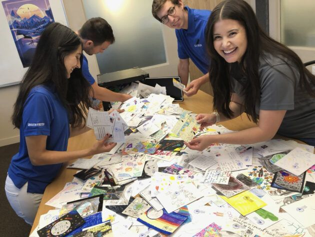 Blue Origin employees who volunteer for the Club for the Future sort postcards. (Blue Origin Photo)