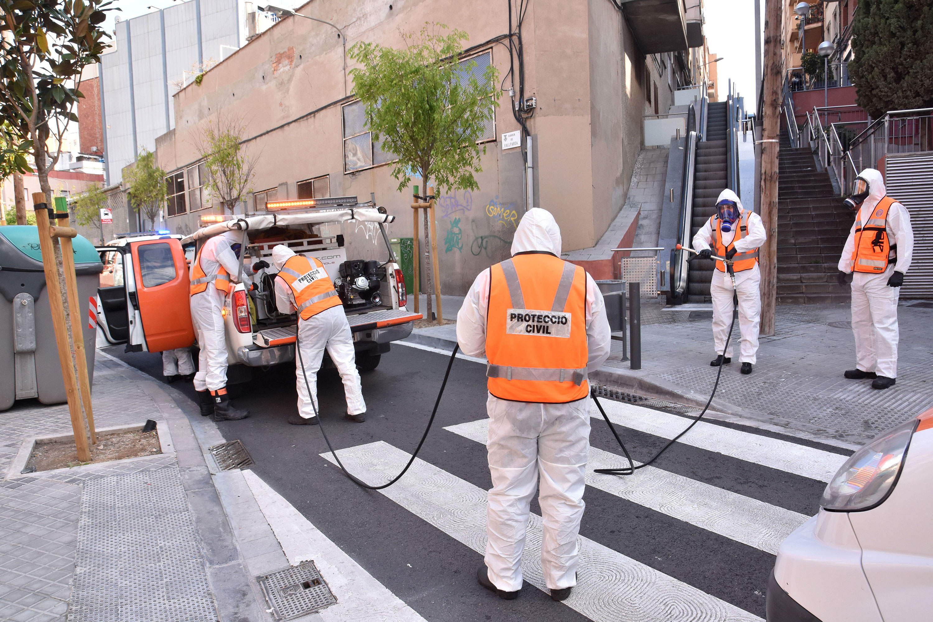 A group of civil protection volunteers from disinfects a street in L´Hospitalet, Spain, on March 27.