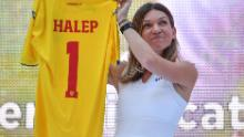 Halep holds up a Romanian national football team jersey presented to her by the Romanian Football Federation,