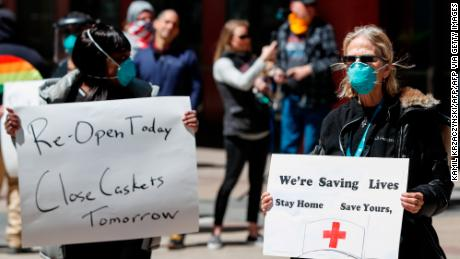 A registered nurse holds a sign during a protest demanding to reopen the Illinois economy on May 1 in Chicago.