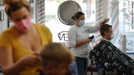 A hairstylist cuts the hair of a customer at a recently reopened barber shop in Fort Lauderdale, Florida, on May 18.