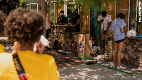People clean up broken glass and debris outside McCormick & Schmick's restaurant in downtown Atlanta, Georgia, on Saturday, May 30. The building was vandalized during Friday night's protests over the death of George Floyd.
