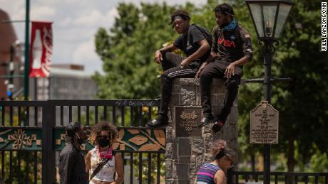 Protesters sit on a pillar at the entrance of Centennial Olympic Park in downtown Atlanta on May 30.