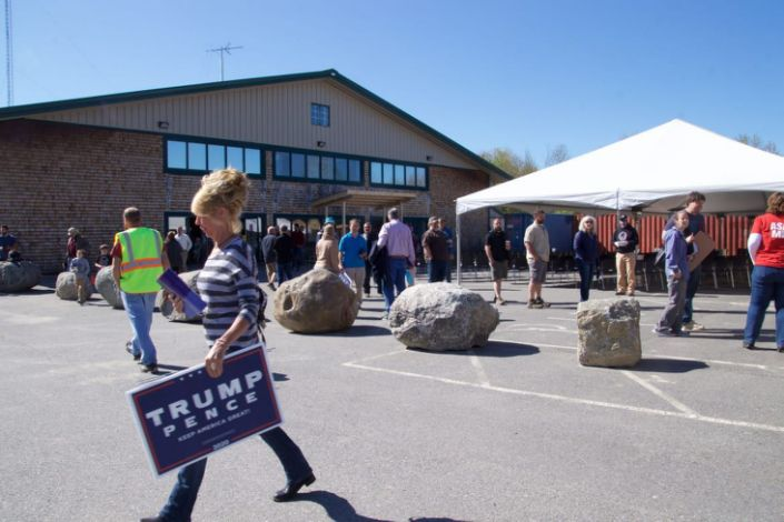 "<div class=""inline-image__caption""> <p>A woman carries a Trump campaign sign following indoor services held at Calvary Chapel May 24 in Orrington, Maine. The signs and other campaign literature were available in the parking lot of the church before and after services May 24, which were held in defiance of state mandates.</p> </div> <div class=""inline-image__credit""> Johanna S. Billings </div>"