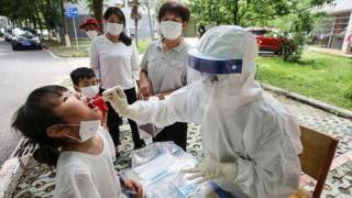 A medical worker takes a swab sample from a child to be tested for coronavirus in a street in Wuhan
