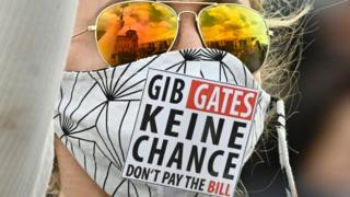 """A protester wears a mask which says in German and English: """"GIB GATES KEINE CHANCE DON'T PAY THE BILL"""""""