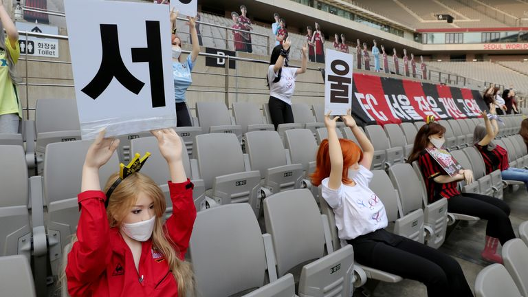 Mannequins, some sex dolls and some holding signs advertising porn sites, in the stadium