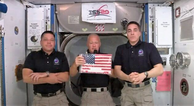 NASA astronaut Doug Hurley shows off the U.S. flag that was left aboard the International Space Station in 2011 by the last space shuttle crew. Hurley and Behnken, at left, will take the flag back to Earth with them aboard their SpaceX Crew Dragon capsule. The space station's current commander, NASA astronaut Chris Cassidy, is at right. (NASA via YouTube)