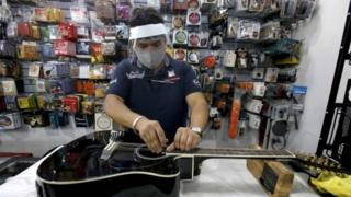 An employee cleans a guitar at a musical instruments store in Guadalajara, Jalisco State, on June 1, 2020 after Mexico began gradually reopening its economy after more than two months of shutdown because of the COVID-19 coronavirus pandemic