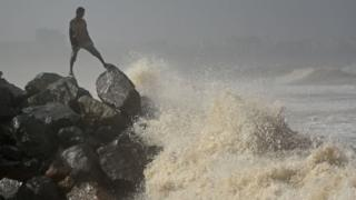 A man on a rock on the seashore while high tide at Versova