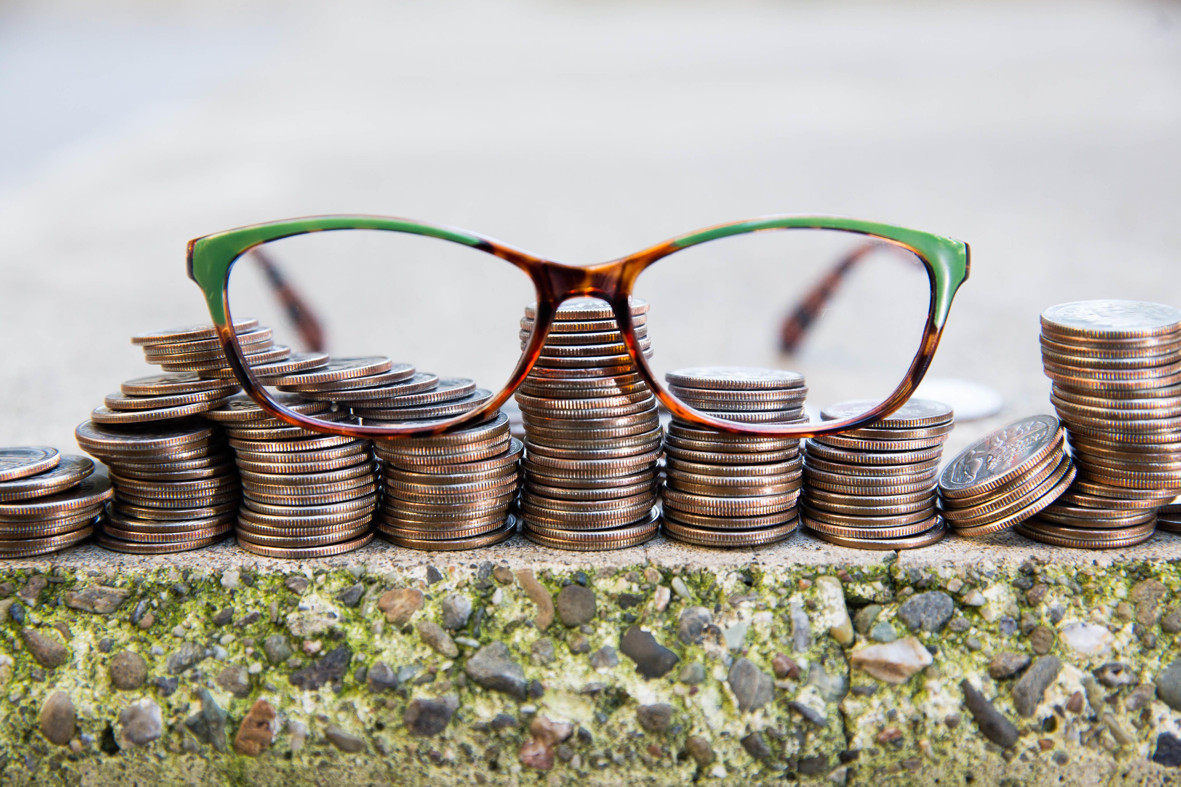 Stacks of coins, with eyeglasses