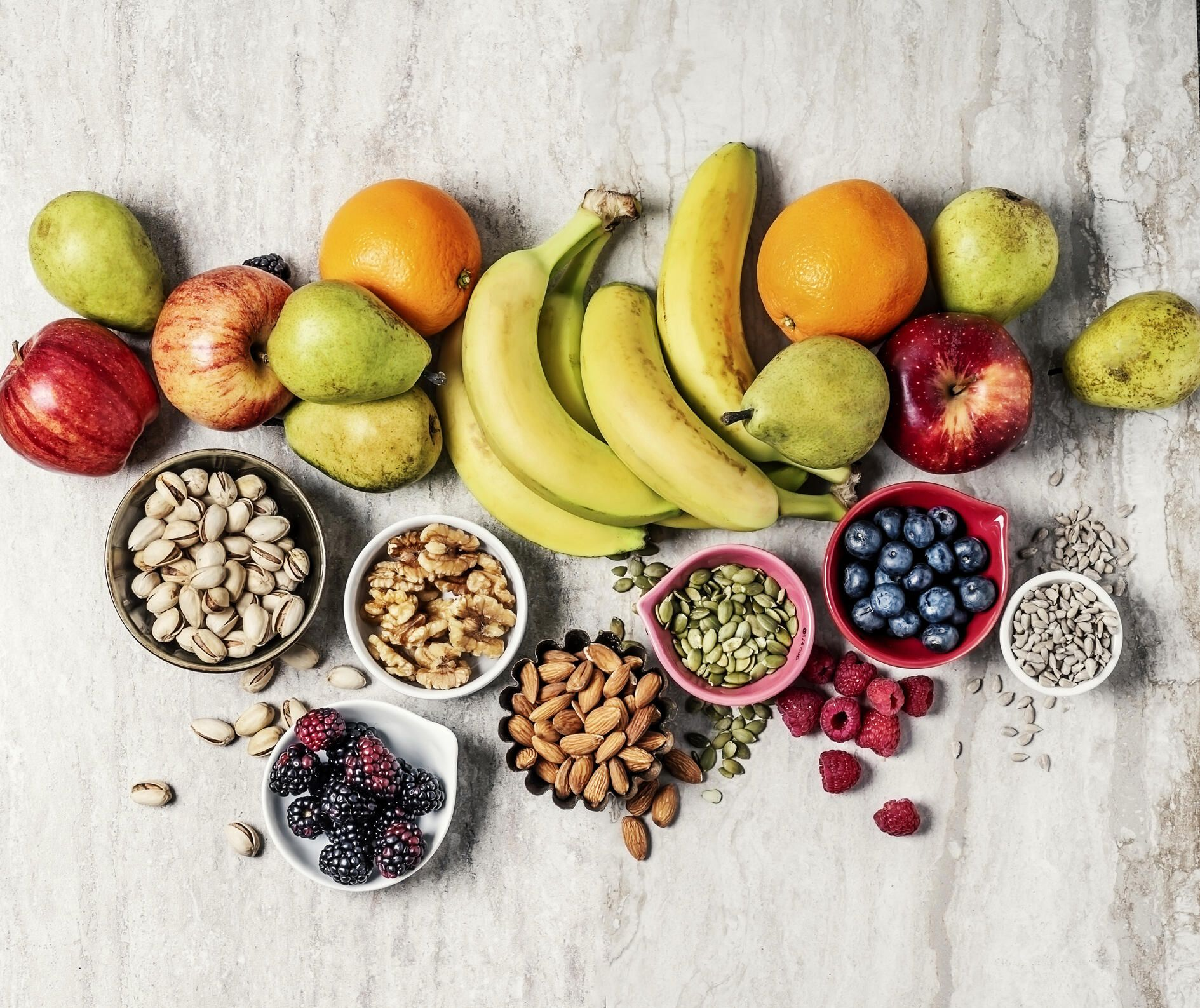 bird's eye view of fruits, nuts and seeds on a granite countertop