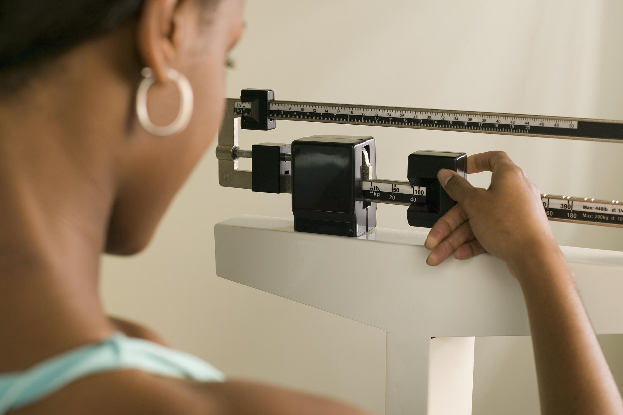 woman checking her weight on a manual scale
