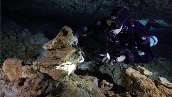 A diver examines a landmark of piled stones left in the oldest ochre mine ever found in the Americas, used 10,000 to 12,000 years ago by the earliest inhabitants of the Western Hemisphere to procure the ancient commodity.
