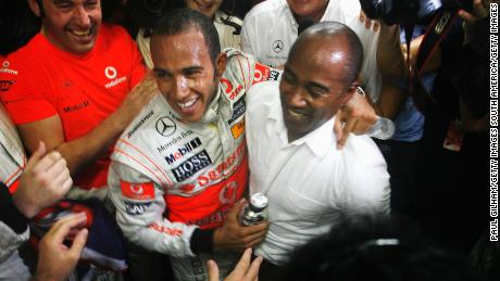 Hamilton celebrates with his father Anthony Hamilton (R) in his team garage following the Brazilian Grand Prix at the Interlagos Circuit on November 2, 2008 in Sao Paulo, Brazil.