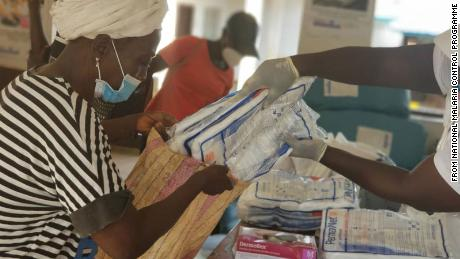 A Red Cross volunteer helps prepare packs of treated bed nets to be distributed to community members in Sierra Leone.