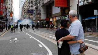 A couple hugs each other as police fire tear gas into the crowds to disperse anti-national security law protesters during a march at the anniversary of Hong Kong