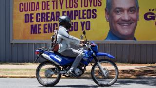 People pass an election campaign poster of presidential candidate Gonzalo Castillo in Santo Domingo, Dominican Republic, 05 June 2020.