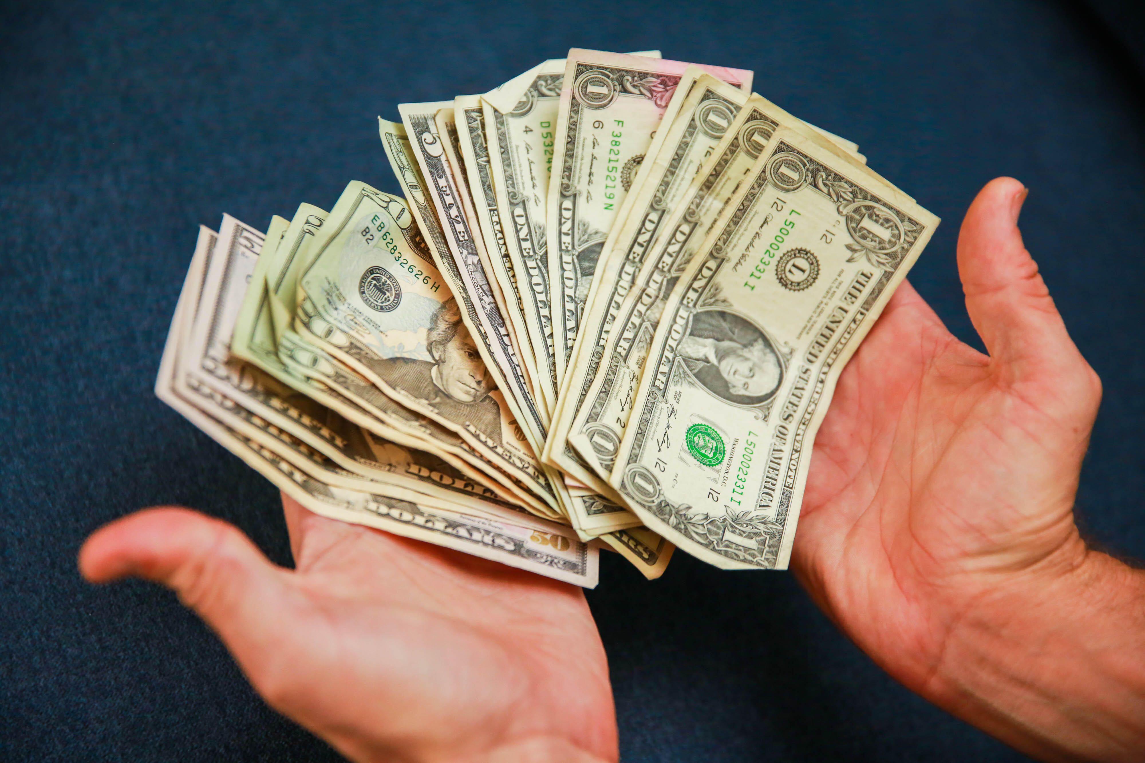 003-counting-cash-money-dollar-bills-hands-blue-background-stimulus-2020