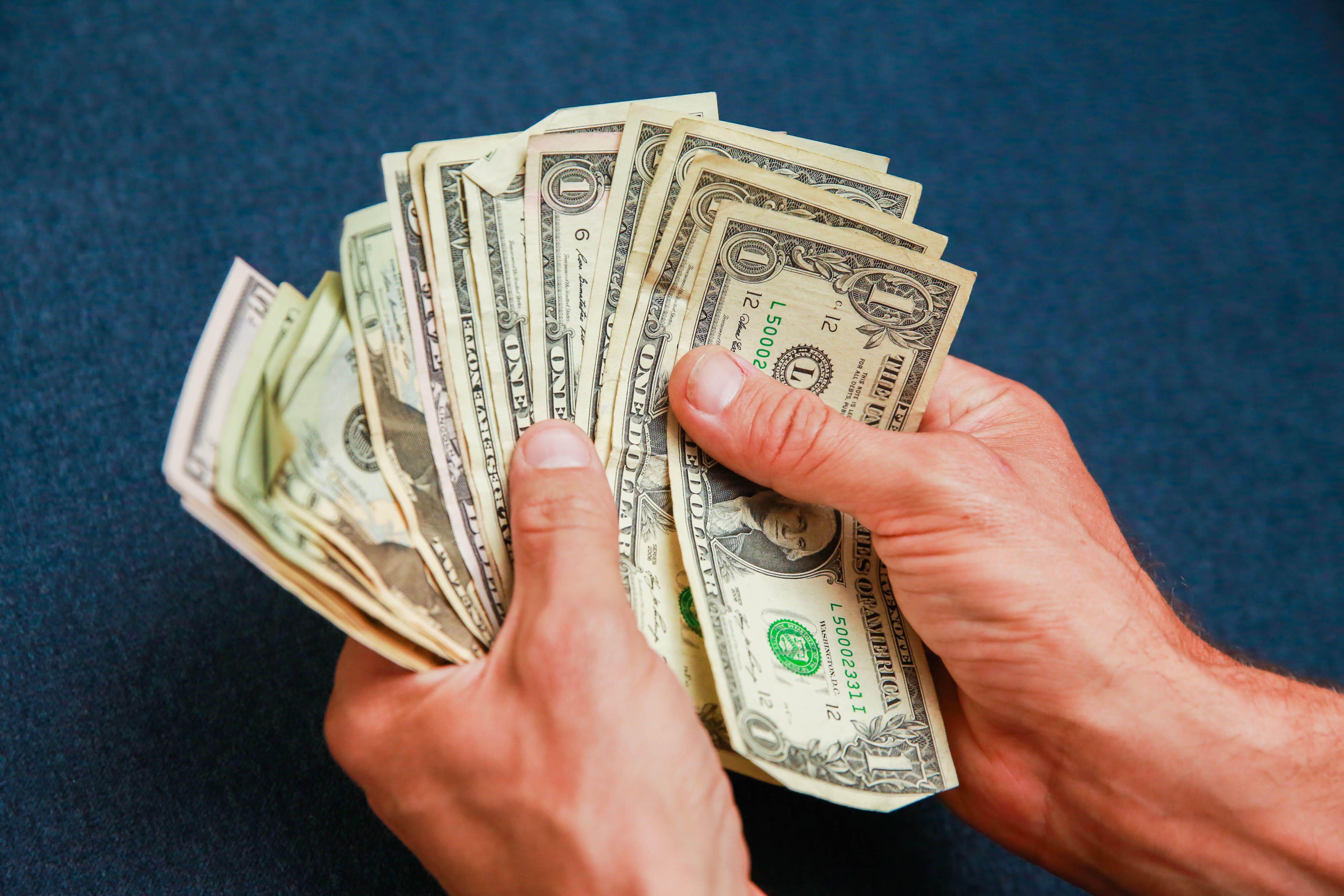 004-counting-cash-money-dollar-bills-hands-blue-background-stimulus-2020