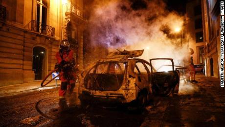 Firefighters extinguish a burning car near the Champs-Élysées following PSG's Champions League final defeat.