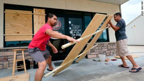 Daoith Porm, left, and Bunsant Khov, right, board their business with Hurricane Laura just hours away.
