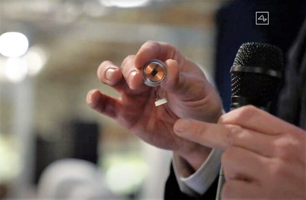 Neuralink co-founder Elon Musk holds a brain implant device between his fingers during a presentation about the technology. (Neuralink via YouTube)
