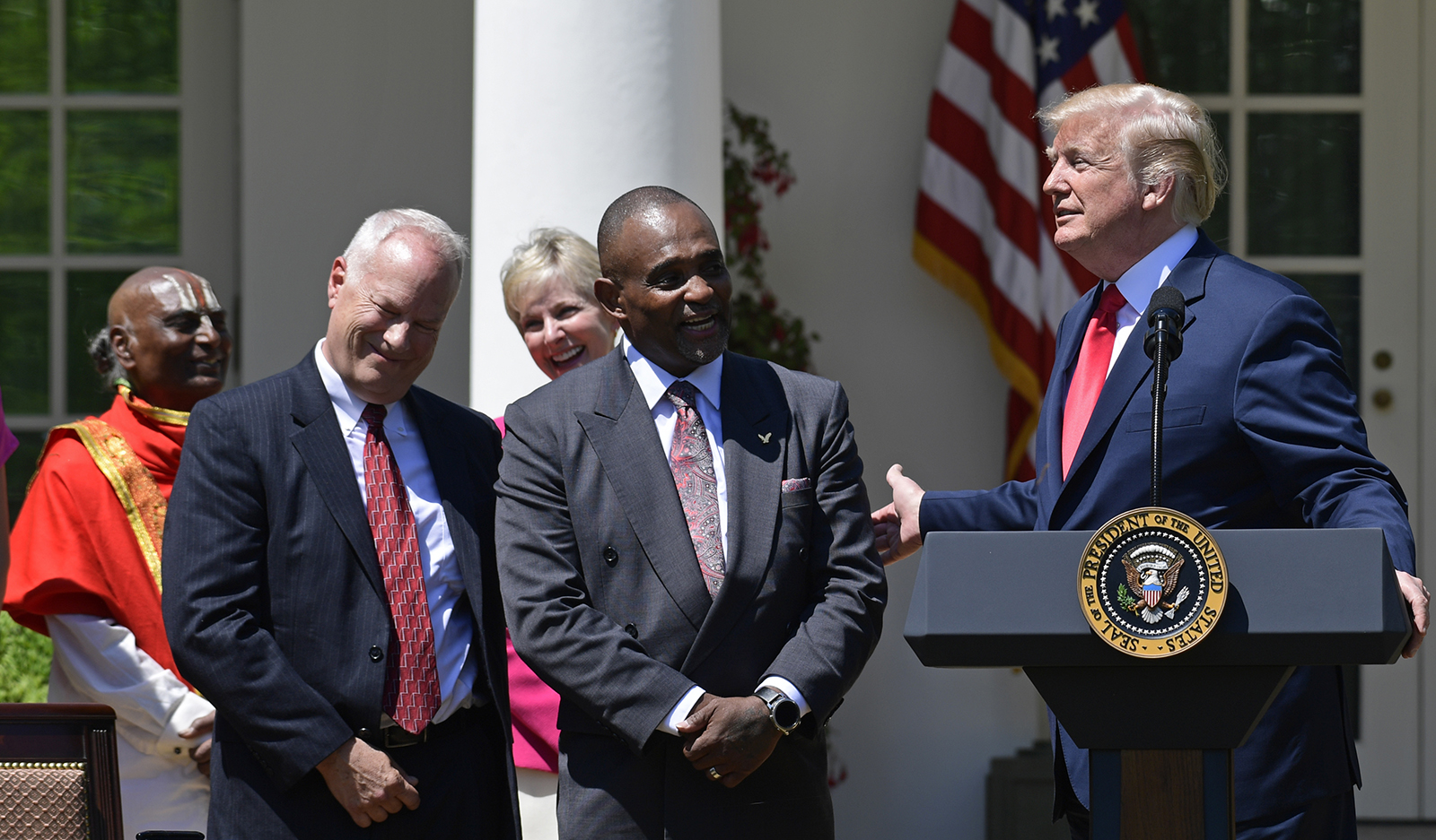 In this May 3, 2018 file photo, President Donald Trump talks about Jon Ponder, center, from Las Vegas during a National Day of Prayer event in the Rose Garden of the White House in Washington.