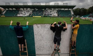 Fans stand on ladders to peer over a wall as they watch Bohemians 1905 in June.