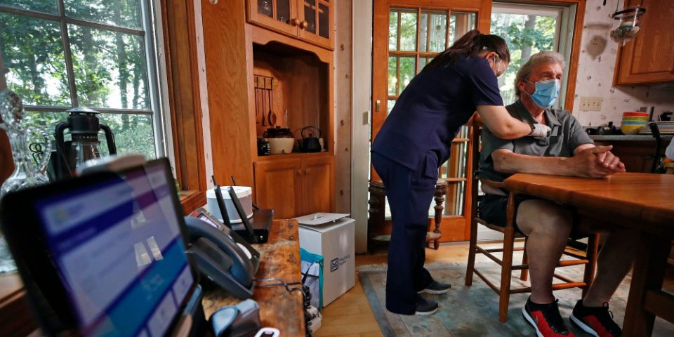 "Nurse practitioner Sadie Paez listens to the heart of William Merry, who is recovering from pneumonia at his home, Thursday, July 9, 2020, in Ipswich, Mass. <p class=""copyright"">AP Photo/Elise Amendola</p>"