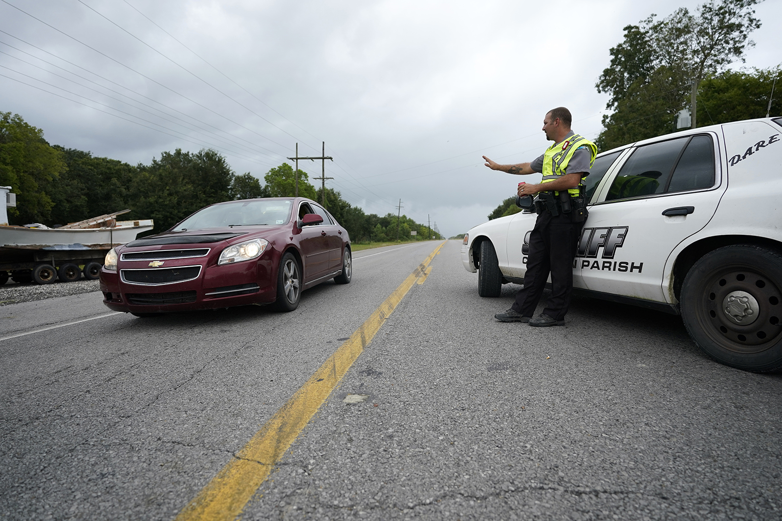 A Cameron Parish Sheriff's deputy waves at a roadblock on LA 27 as residents evacuate Cameron in Lake Charles, Louisiana on Wednesday, August 26, ahead of Hurricane Laura.