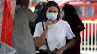 A woman wearing a protective face mask leaves after her swab samples are taken by volounteering firefighters at a test station for Covid-19 coronavirus in Marseille, France,