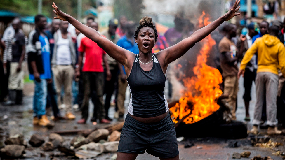 An opposition supporter in front of a burning barricade in Nairobi as a group of demonstrators blocked the road and tried to prevent voters from accessing a polling station during presidential elections - 26 October 2017