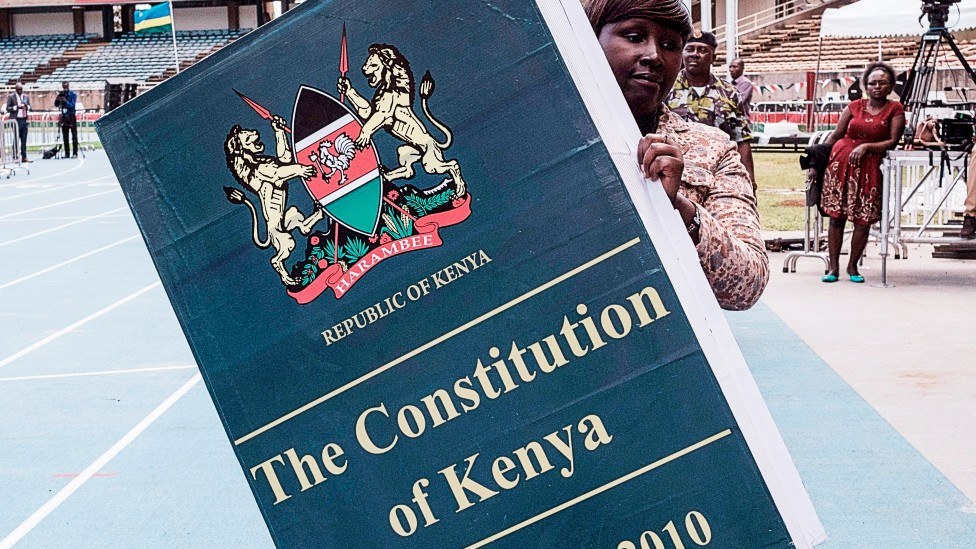 A woman carries a giant replica of the constitution of Kenya ahead of a presidential inauguration ceremony in Nairobi - 17 November 2017