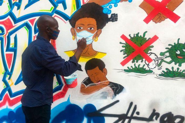 Congolese artist Chris Shongo paints a mural in Kinshasa.