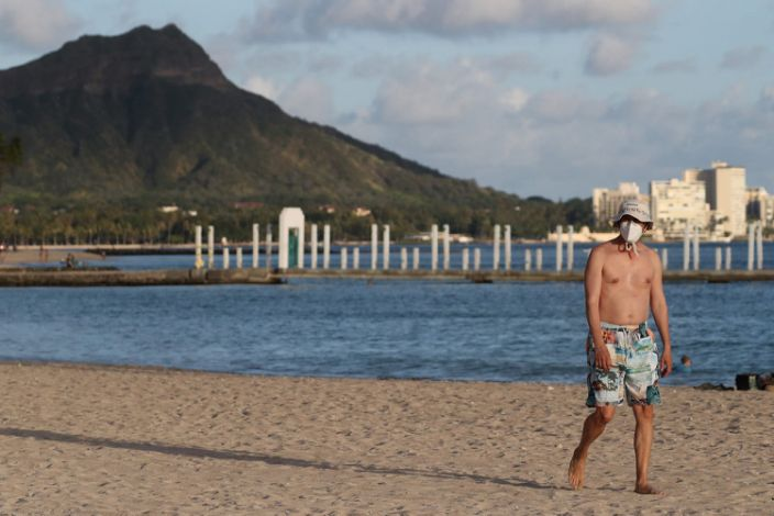 "A beachgoer wearing a protective mask walks down Waikiki Beach, with Diamond Head mountain in the background in Honolulu, Hawaii, on April 28, 2020. <p class=""copyright"">Reuters/Marco Garcia</p>"