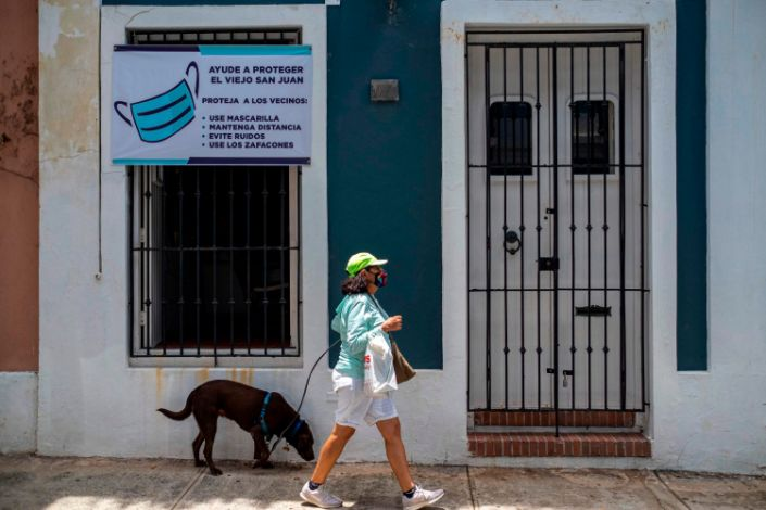 "A woman walks pass by a banner urging visitors to wear face masks in San Juan, Puerto Rico. <p class=""copyright"">Ricardo Arduengo/AFP/Getty Images</p>"