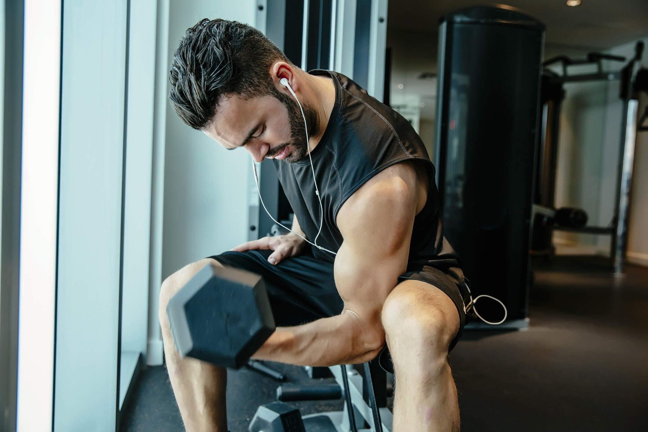 A young man performing bicep curls at the gym.