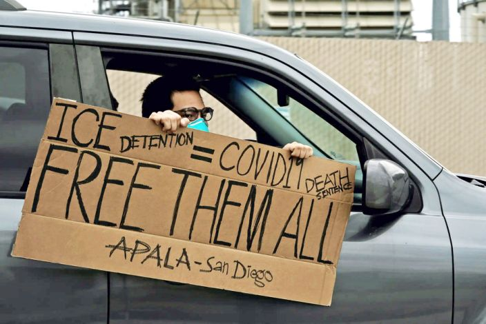 """A protestor holding a sign reading ''ICE Detention = COVID19 Death Sentence'' is driven past the Otay Mesa Detention Center, a ICE (Immigrations & Custom Enforcement) federal detention center privately owned and operated by prison contractor CoreCivic, amid the coronavirus disease (COVID-19) outbreak in San Diego, California, U.S., April 11, 2020. <p class=""""copyright"""">REUTERS/Bing Guan</p>"""