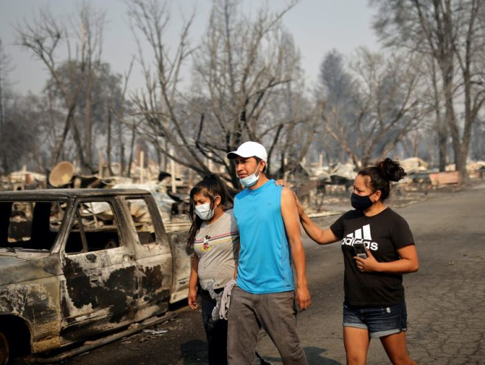 """Sandra and Daniela Reyes comfort Isaias Reyes while visiting their damaged trailer home after the wildfires destroyed a neighborhood in Bear Creek, Phoenix, Oregon, U.S., September 10, 2020. <p class=""""copyright"""">Carlos Barria/REUTERS</p>"""