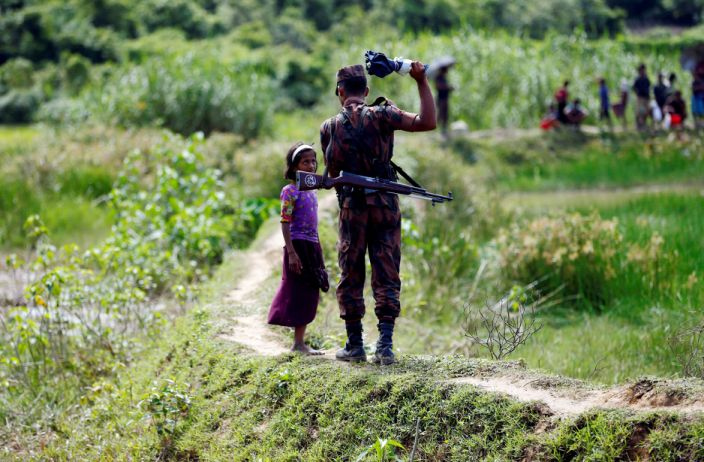Image: A member of Border Guard Bangladesh (BGB) tells a Rohingya girl not to come on Bangladesh side, in Cox's Bazar (Mohammad Ponir Hossain / Reuters file)