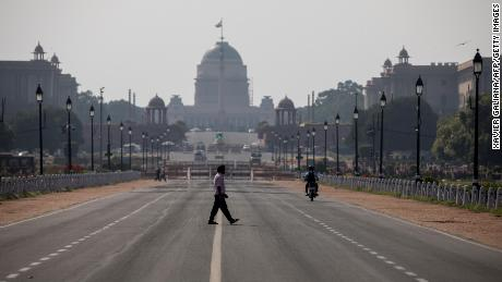 A man crosses a deserted Rajpath in New Delhi on March 22, 2020.