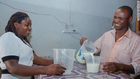 Shopkeeper Kioko Mwange, right, from eastern Kenya, serves fresh milk to a customer.