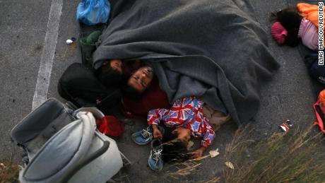 A family sleeps at a parking space, following a fire at the Moria camp.