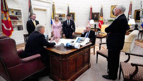 In this White House photo from December 2019 provided by Bob Woodward, President Donald Trump is seen speaking to Woodward in the Oval Office, surrounded by some aides and advisers, as well as Vice President Mike Pence. On Trump's desk is a large picture of Trump and North Korean leader Kim Jong Un.