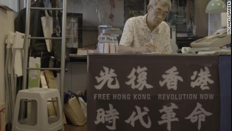 Lam Wing-kee in his Taipei book shop, where a banner displays slogans which have been declared subversive in Hong Kong.