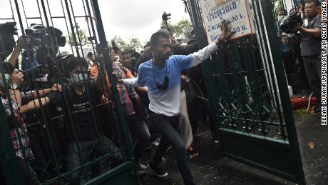 Anti-government protesters break through a gate at Thammasat University as they arrive for a pro-democracy rally in Bangkok on September 19.